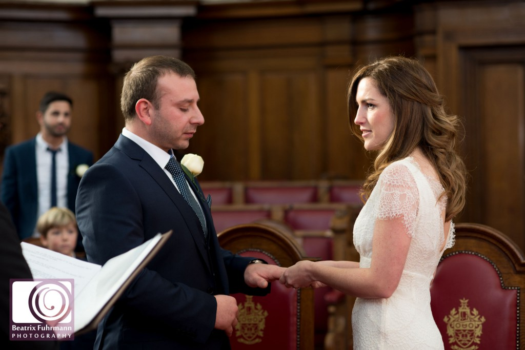 Islington Town Hall wedding ceremony - bride and groom exchanging rings