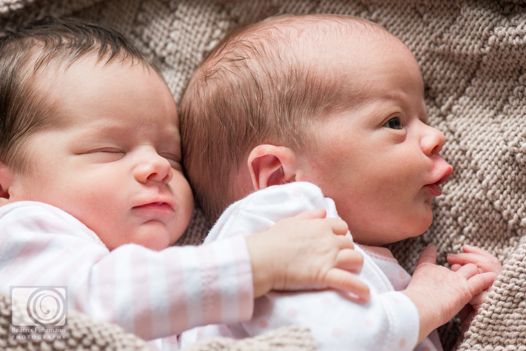 Newborn twin girls cuddling