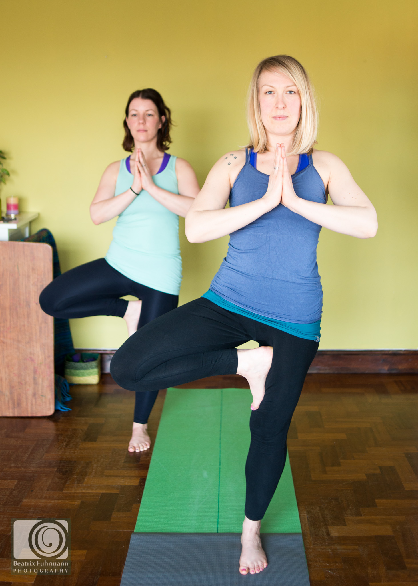yoga teacher and student in tree pose