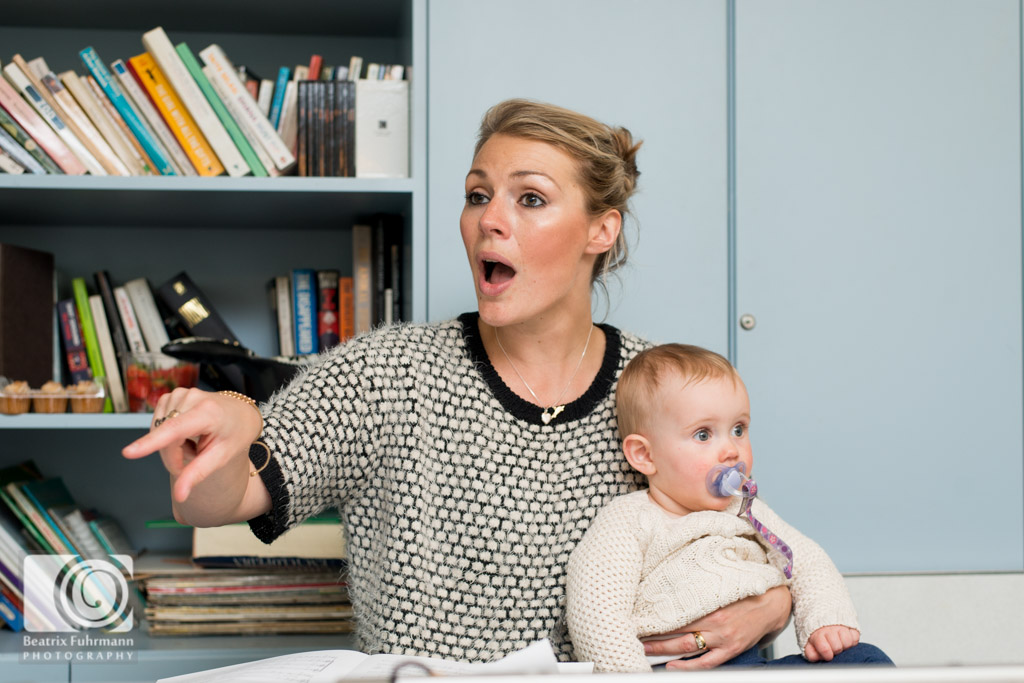 Choir Baby founder Naomi conducting while holding on to her little baby daughter