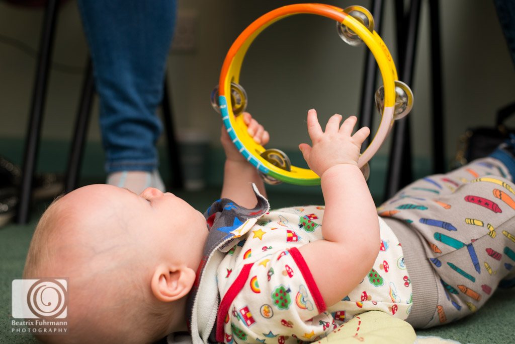 Baby playing with a tambourine