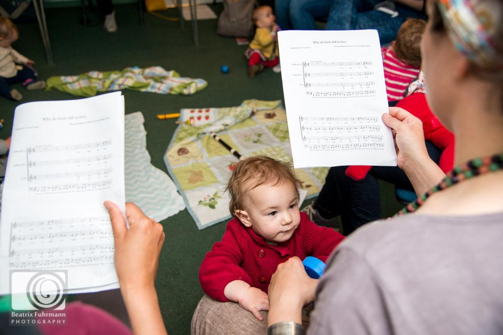 Toddler and mums holding score sheets for singing