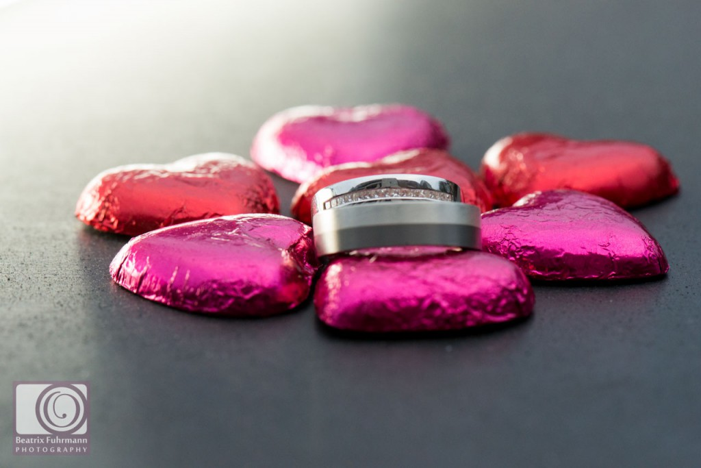 Wedding rings and chocolate hearts close up