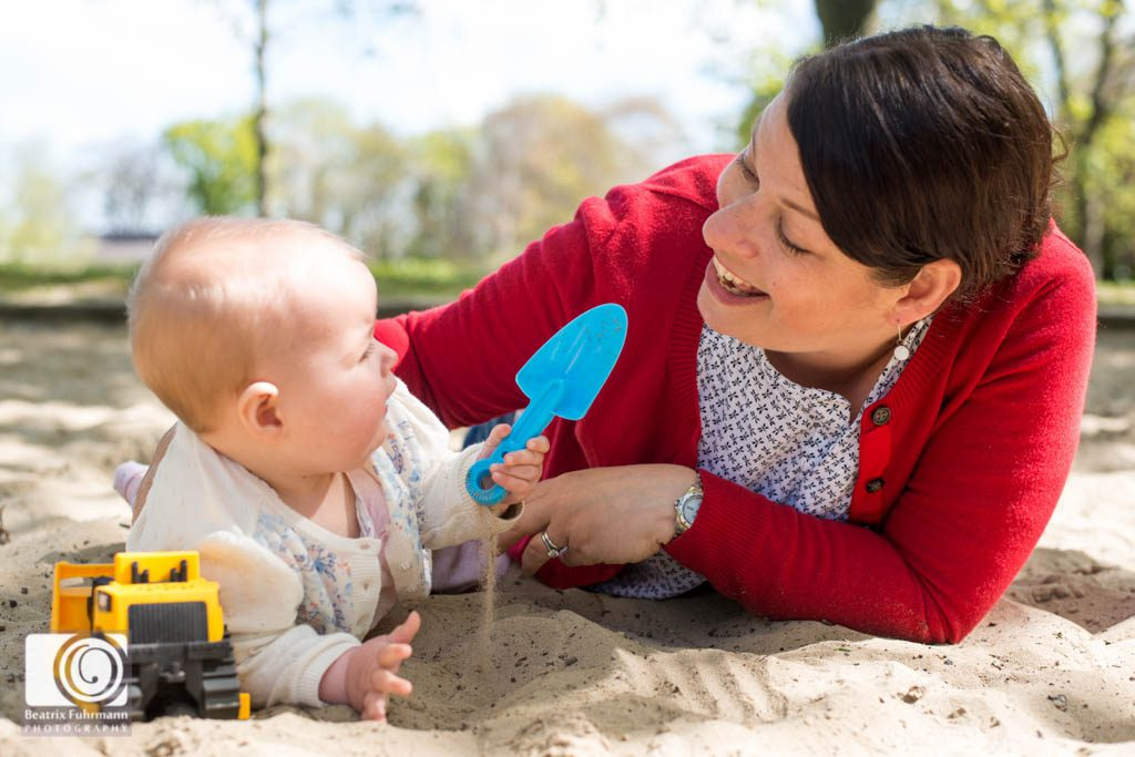 Baby girl and mummy in having fun in the sand pit - family photography london