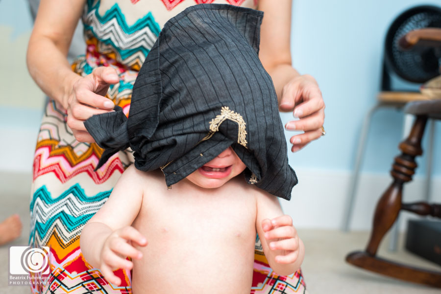 Outfit change - little boy crying with shirt stuck over his head