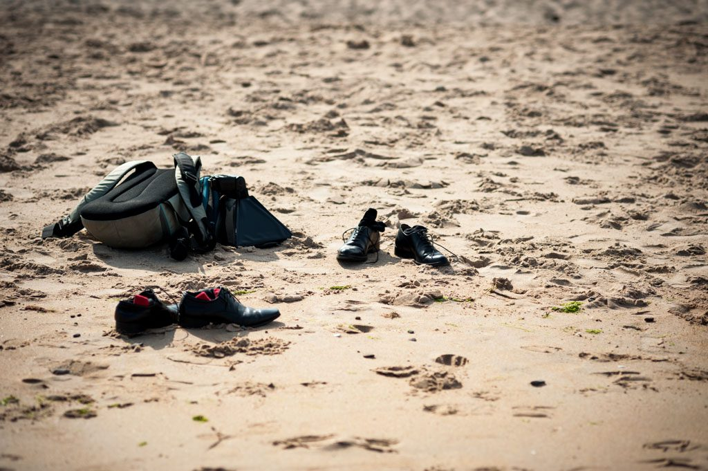 photographer's bag and shoes during a portrait session on the beach