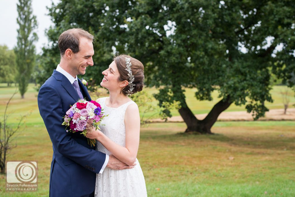 Bride and groom smiling at each other in an embrace on the Muswell Hill Golf Course