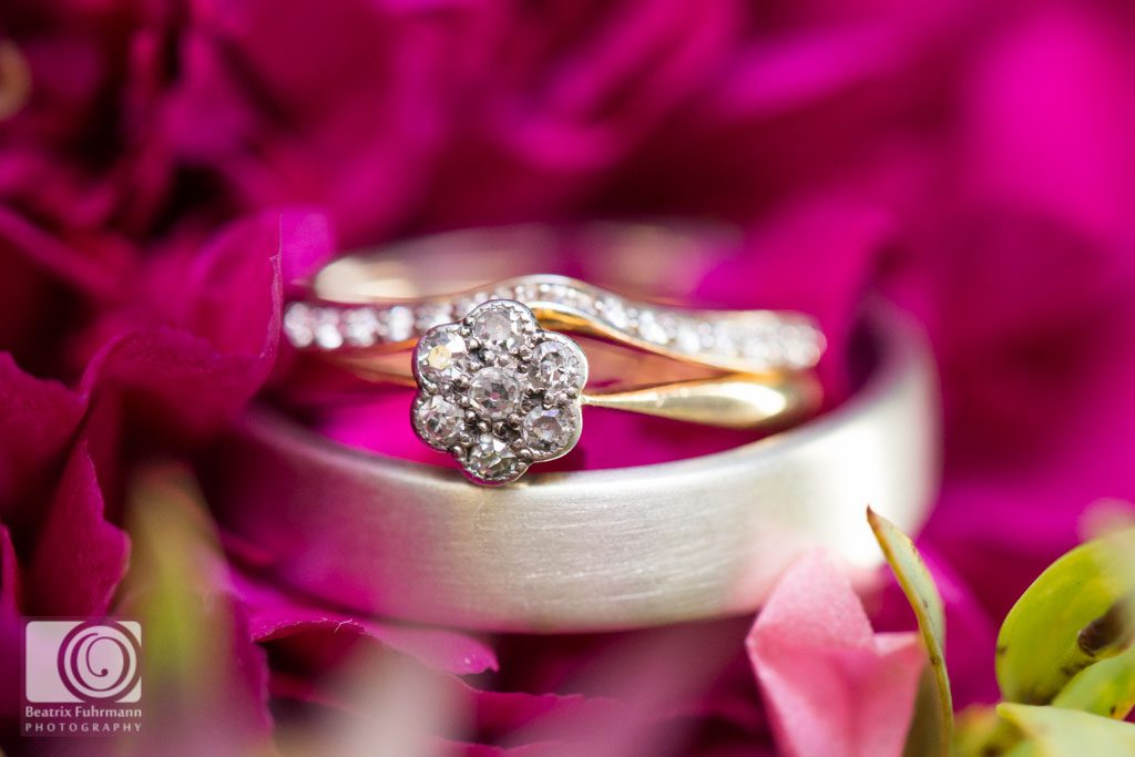 wedding rings and flower engagement ring on the wedding bouquet