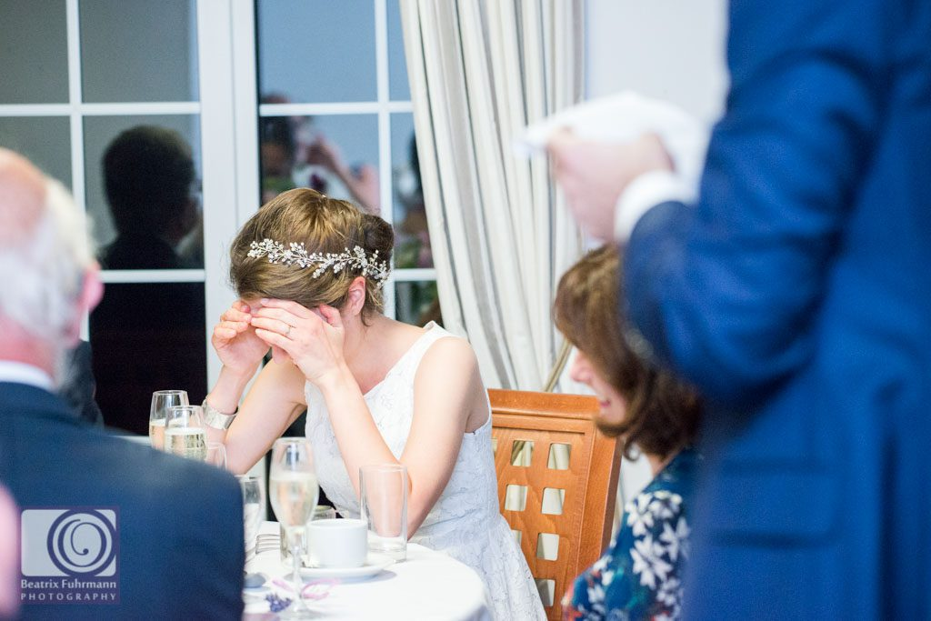 Bride bowing her head during wedding speech