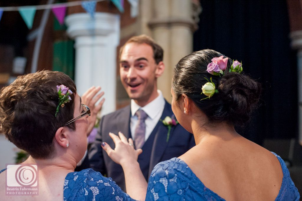 Groom having a moment of laughter with the bridesmaids
