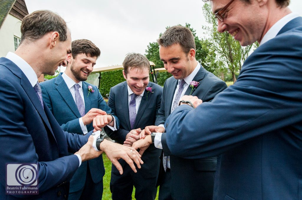 Groomsmen syncing the time of their watches, a gift from the gro