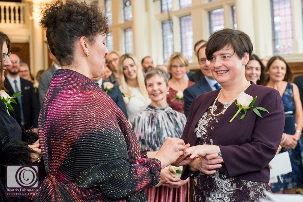 Brides exchanging rings at their Old Finsbury Town Hall wedding