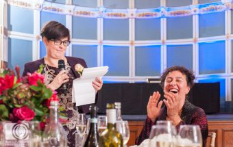 Bride laughing at her wife's wedding speech