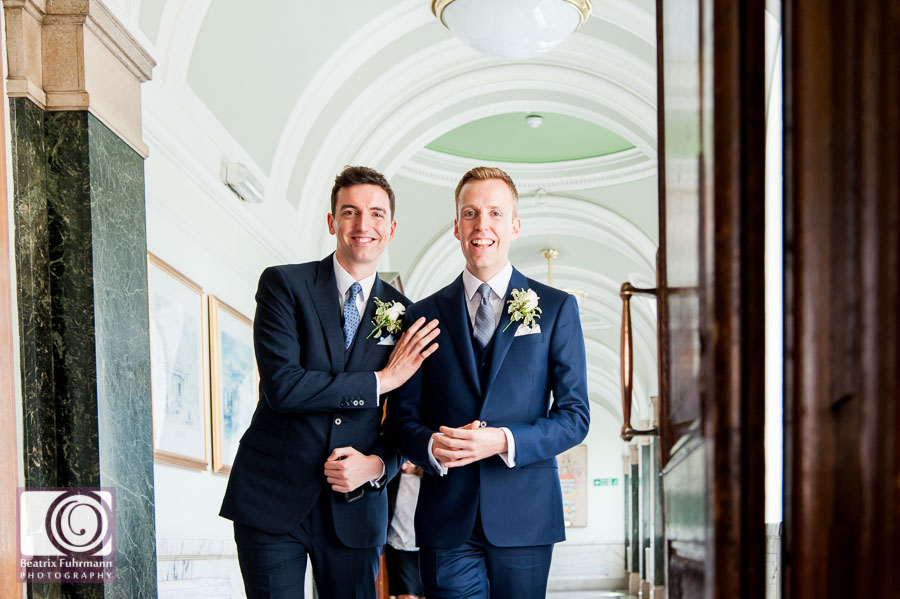 Grooms walking down the gallery at Islington Town Hall - Gay London wedding