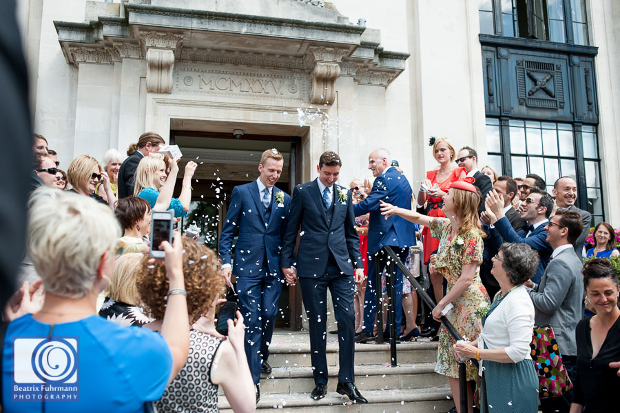 Grooms showered in confetti outside the Islington Town Hall