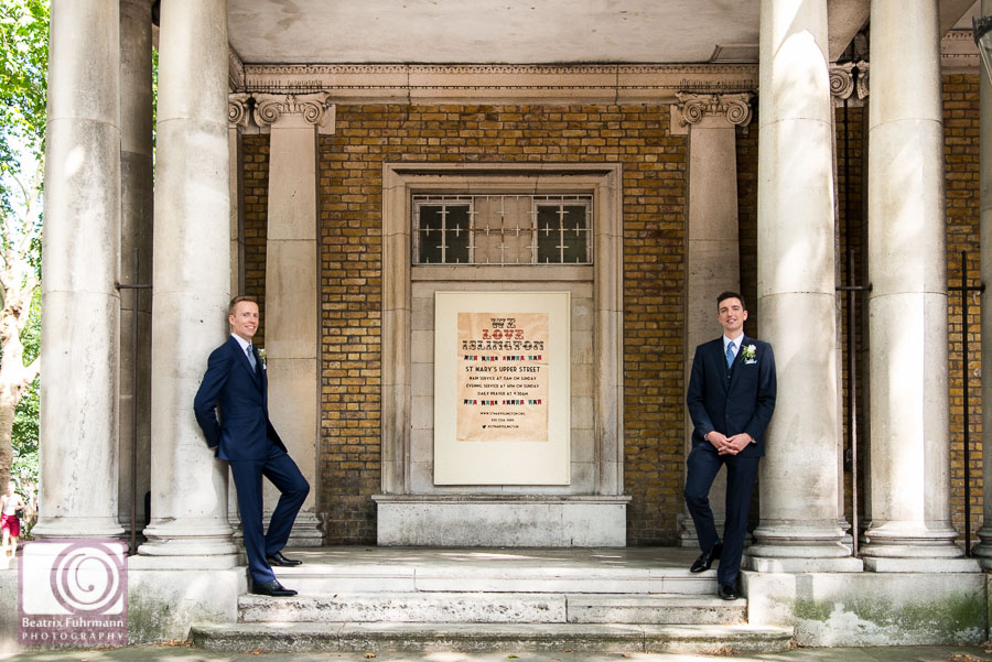 Grooms leaning against St. Mary's Church's columns - Gay London wedding photography