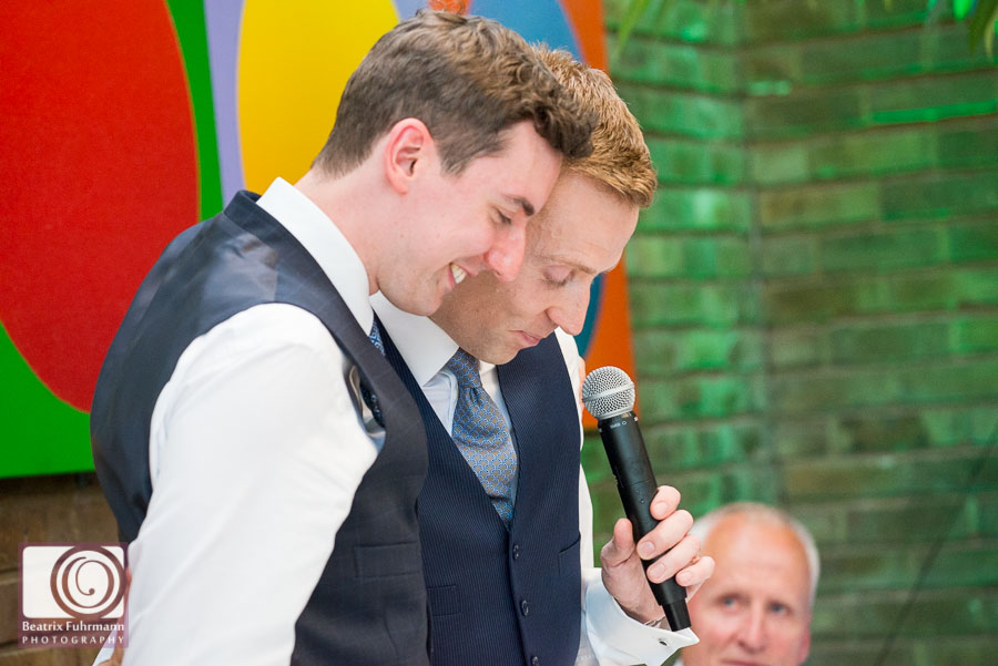 Groom being supported by his husband as he is choking up during his speech - Gay London Wedding photography
