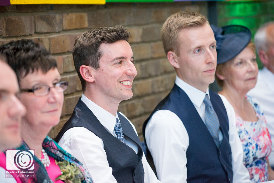 Grooms smiling at the best man's speech