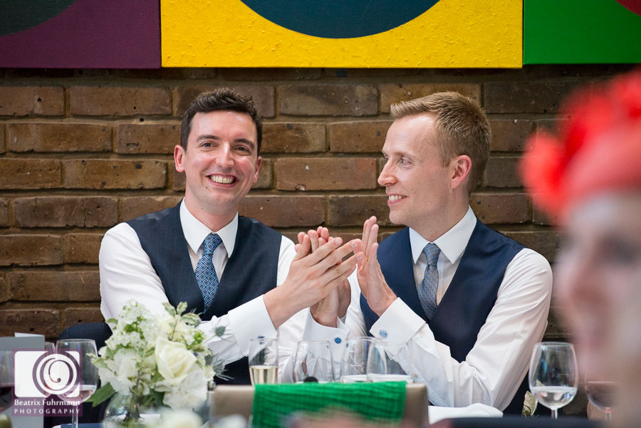 Grooms applauding best man's speech