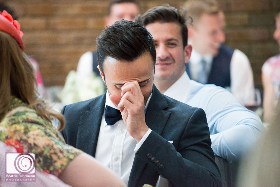 Wedding guest laughing and bowing his head