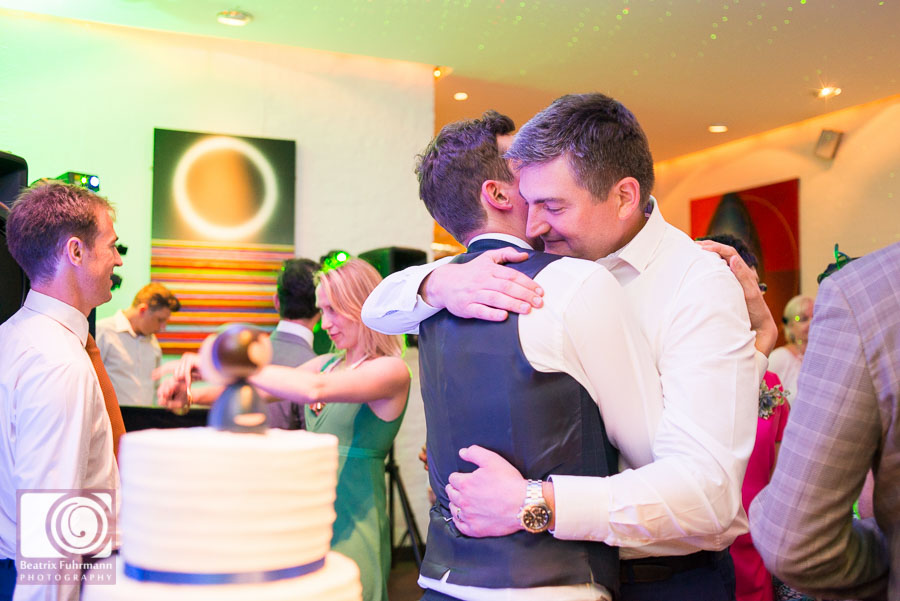 Groom and best man hugging on the dance floor