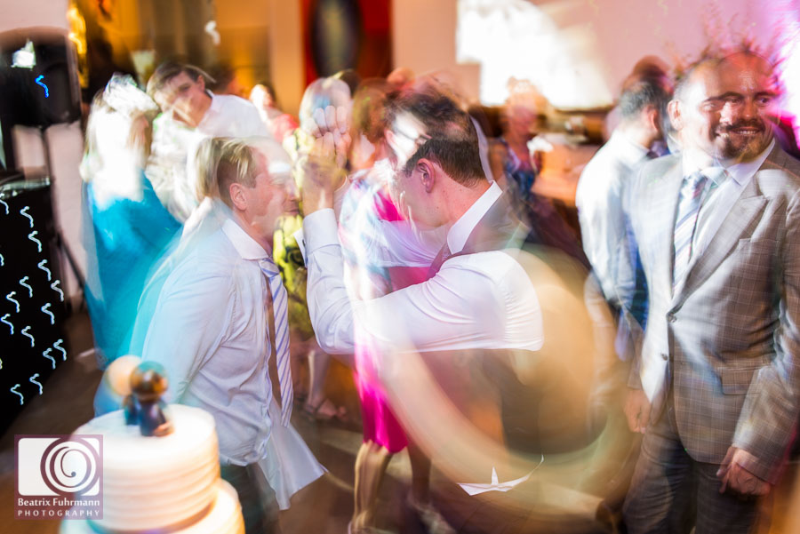 Wedding guests and groom dancing