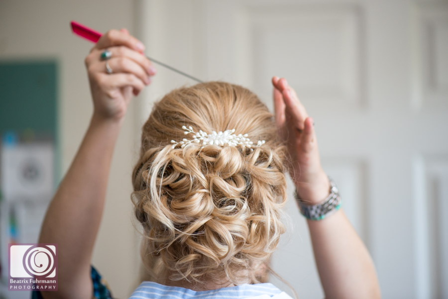 Hair stylists hands adjusting bridal hair to a curly knot with gorgeous hair piece