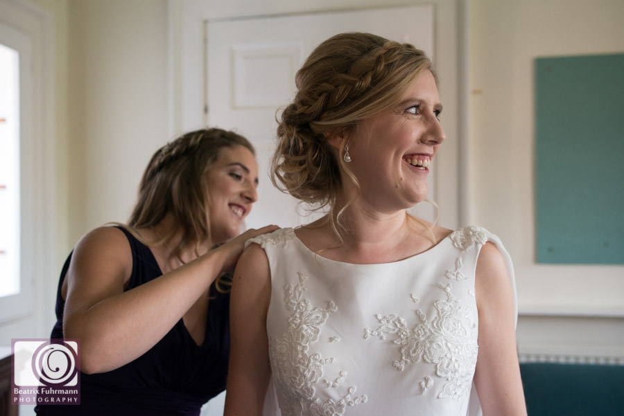 Smiling bride as she is getting into her lace applique wedding dress