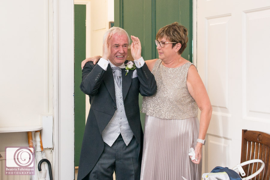 Crying father of the bride as he greets his daughter in her gorgeous wedding dress