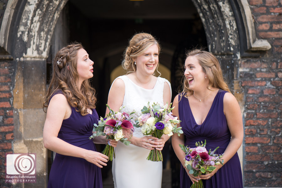 Bridesmaids in purple dresses and bride giggling