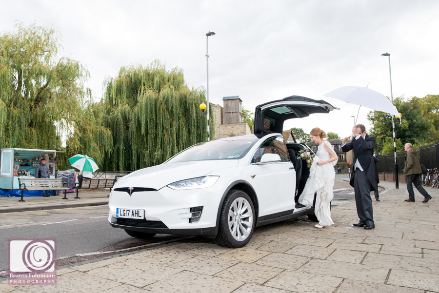 Bride and groom getting into a white Tesla car