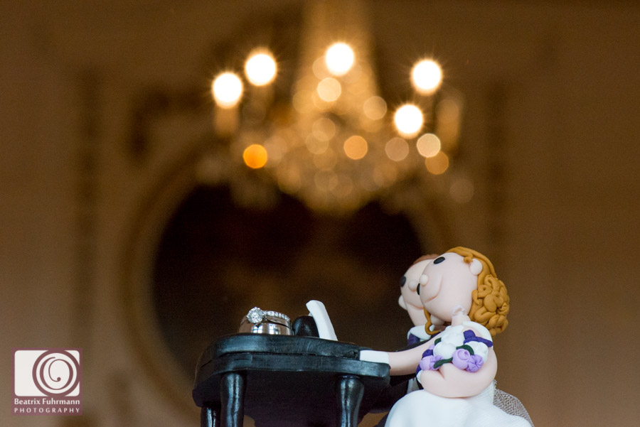 Personalised caketopper - couple sitting on the piano - with wedding rings and chandelier in the background