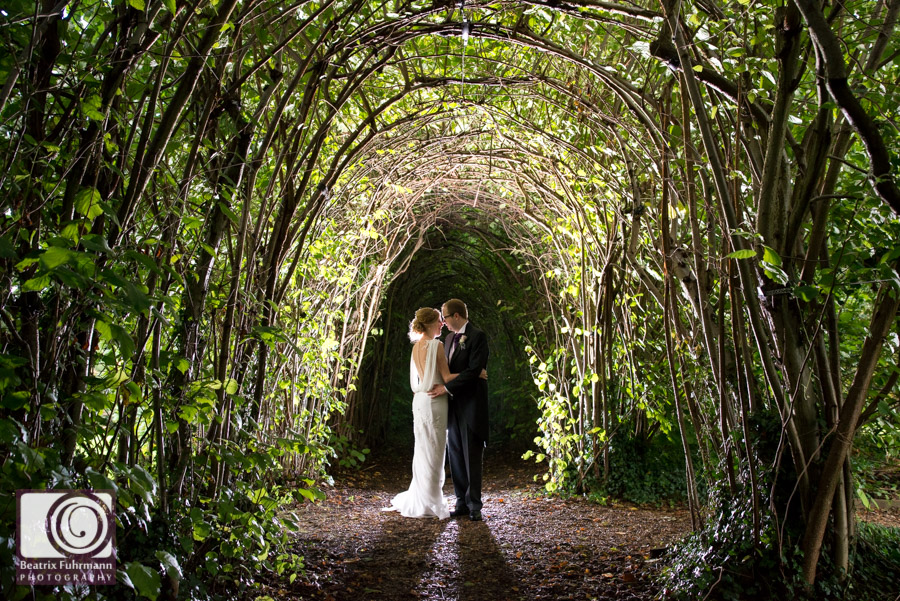 Bride and groom in fairytale-like, green tunnel near Madingley Hall's rose garden