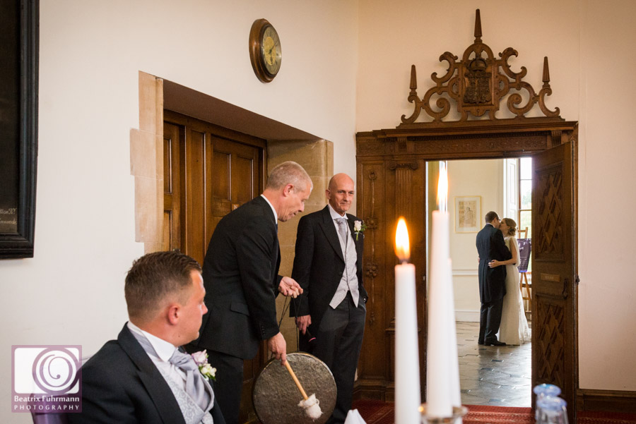 Groom kissing his bride before entering their Madingley Hall wedding reception