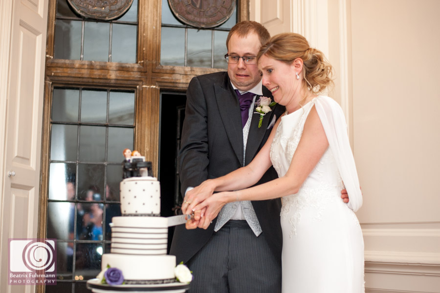 Humorous shot of Bride and groom cutting the cake
