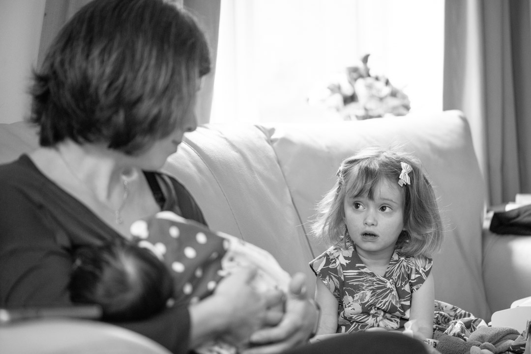 Documentary family photography - Mum breastfeeding her baby and talking to the older sibling