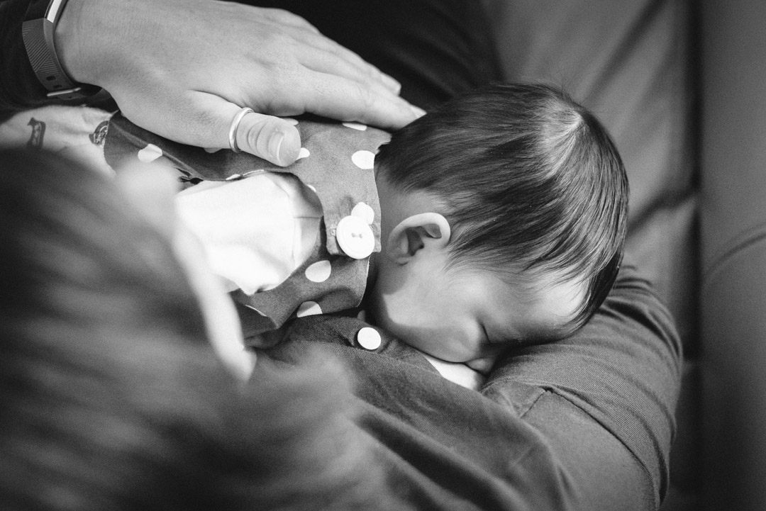 baby breastfeeding with mum's hand caressing her neck