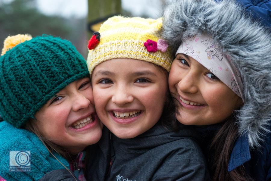 3 Schwestern mit Wollmützen lächeln in die Kamera