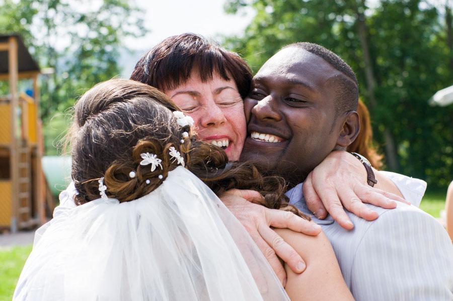 Mutter umarmt Braut und Bräutigam - Tochter und Schwiegersohn