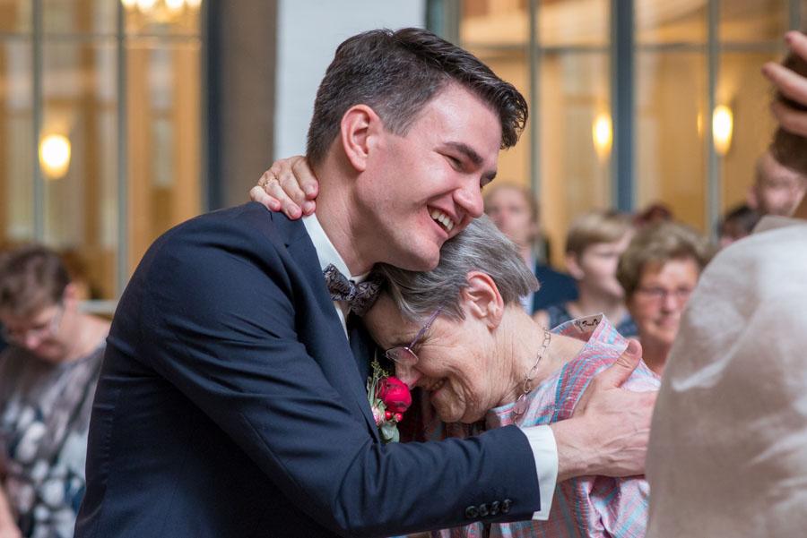 Bräutigam umarmt die Oma seiner Braut