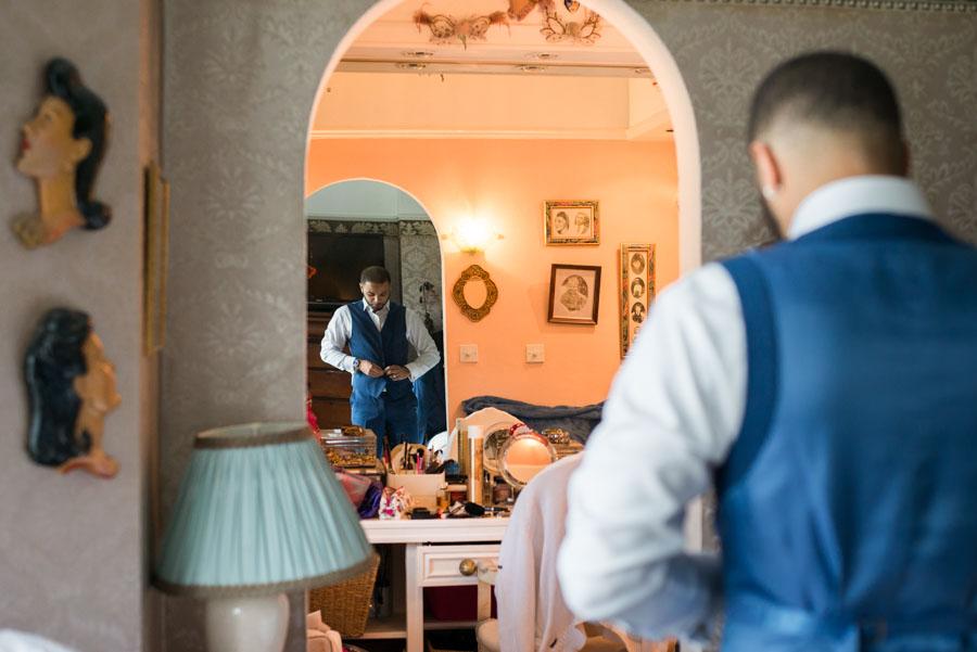 Bräutigam von hintern fotografiert mit Reflektion im Spiegel, beim Ankleiden am Morgen im Elternhaus