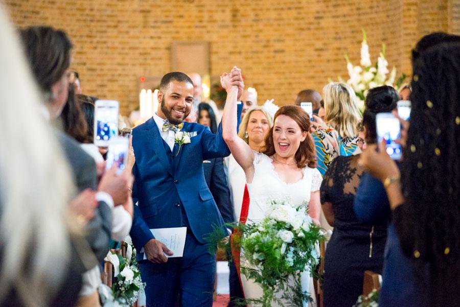 Braut und Bräutigam beim Auszug aus der Kirche, die Arme triumphierend und Hände haltend in der Luft
