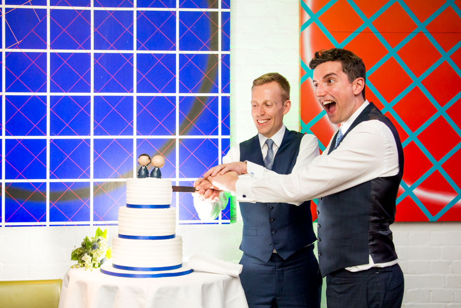 Bräutigame schneiden ihre Hochzeitstorte an