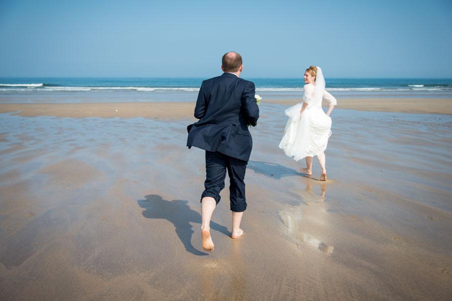 Braut und Bräutigam rennen barfuß im Watt auf das Meer zu