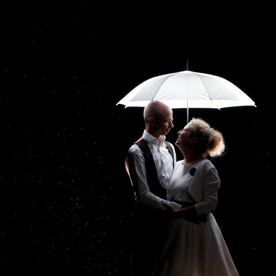 Braut und Bräutigam bei Nacht im Regen unter einem Hell erleuchteten Regenschirm