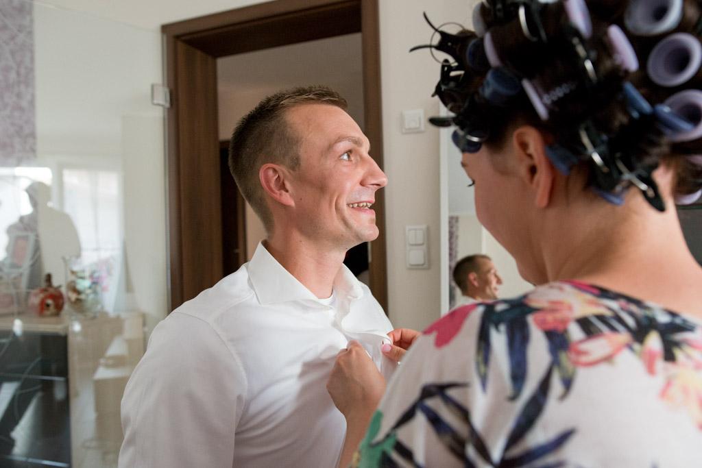 Braut in knöpft das Hemd ihres Bräutigams zu