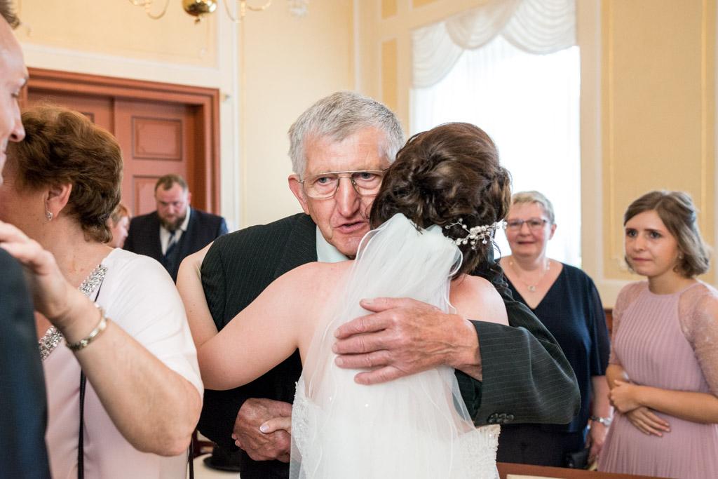 Braut umarmt ihren Opa nach der Trauung