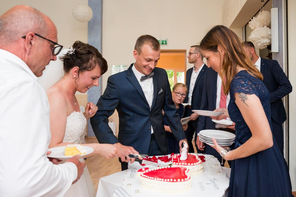 Torsten und Kristin schneiden ihre Hochzeitstorte für die Gäste