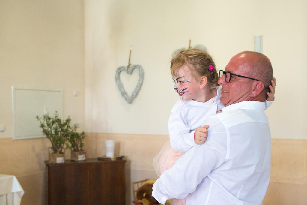 Die Tochter de Brautpaars mit geschminktem Katzengesicht in Opas Armen