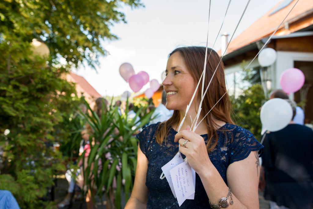 Hochzeitsgast mit Luftballons und lieben wünschen an das Hochzeitspaar
